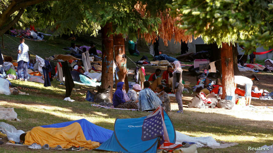 Migrants are seen in a makeshift camp at a park near the San Giovanni railway station in Como, Italy, Aug. 12, 2016.