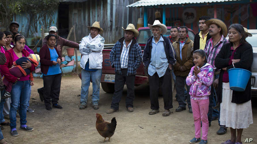 FILE - Villagers gather to talk with Associated Press journalists about their communities and dependence on growing opium to make a living in the Sierra Madre del Sur mountains of Guerrero state, Jan. 26, 2017. Many farmers say they would like to giv