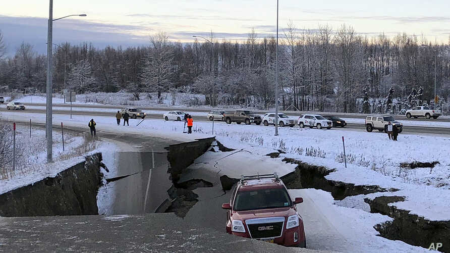 A car is trapped on a collapsed section of the offramp of Minnesota Drive in Anchorage, Nov. 30, 2018.