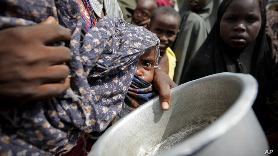 A woman carrying her baby queues for food in a camp established by the Somali Transitional Federal Government for the internally displaced people in Mogadishu.