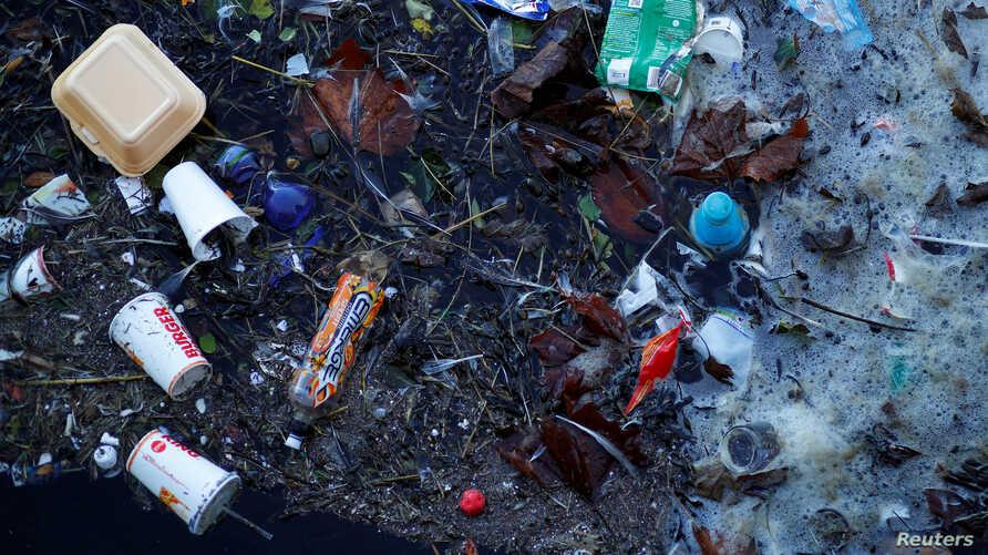 FILE - Plastic and other waste is seen floating on the Marine Lake at New Brighton beach near Liverpool, England, Feb. 11, 2019.