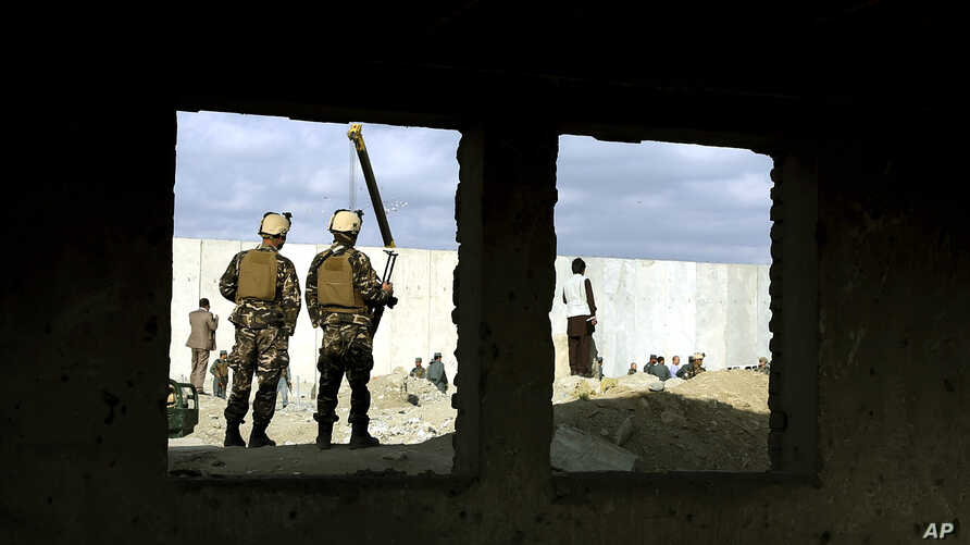 Two Afghan security forces soldiers stand guard at the site of a suicide attack in Kabul, Afghanistan, Oct. 13, 2014.