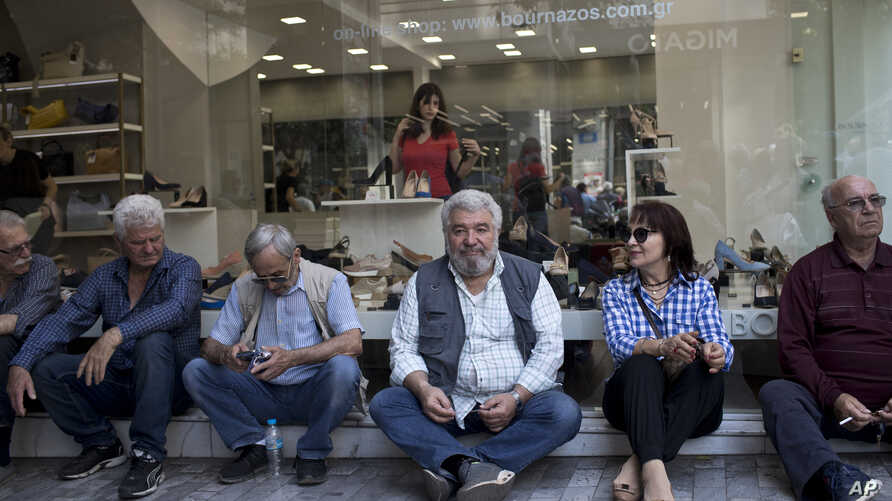 Pensioners sit outside a shoe shop as they take part in a rally near the Finance Ministry in central Athens, April 25, 2018. Thousands of people have taken to the streets of Athens to protest against a number of bailout-related reforms, including the