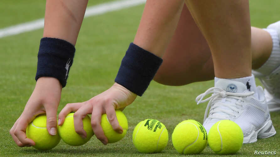 FILE - A ball boy with new tennis balls during a match between USA's Coco Vandeweghe and Germany's Mona Barthel, in Wimbledon, July 4, 2017.