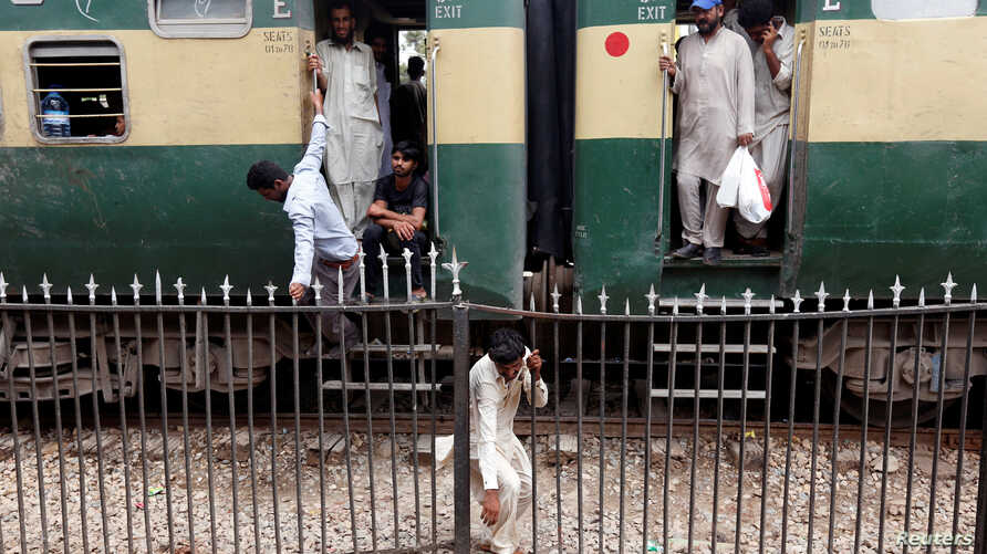 FILE - A man passes through a railing while others board a train as they make their way home at the Cantonment railway station in Karachi, Pakistan, July 5, 2016.