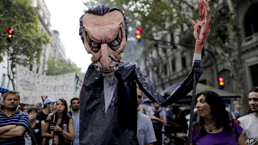 Protesters march holding a giant puppet made doll representing President Mauricio Macri during a demonstration in Buenos Aires, Argentina, March 30, 2017. Unions and social groups are protesting the adjustment policies of Argentina's President.