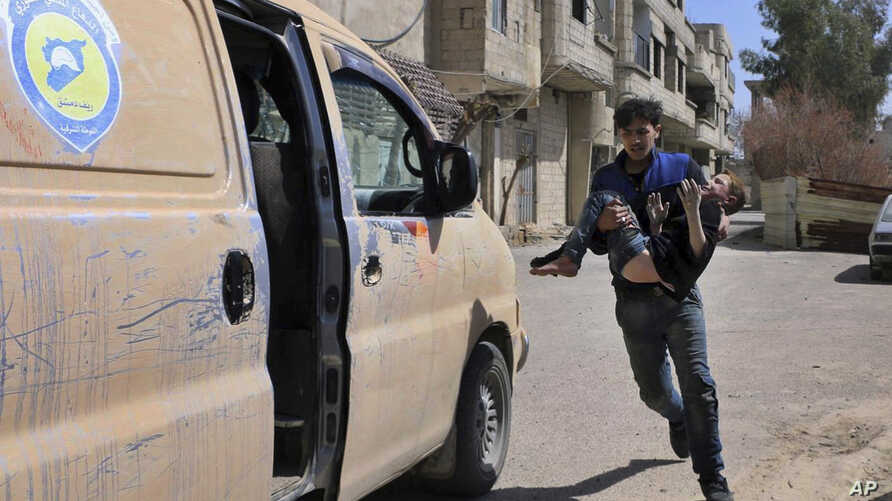 This photo released by the Syrian Civil Defense White Helmets, shows a member of the Syrian Civil Defense group carrying a boy who was wounded during airstrikes and shelling by Syrian government forces in Ghouta, a suburb of Damascus, Syria, Sunday, ...