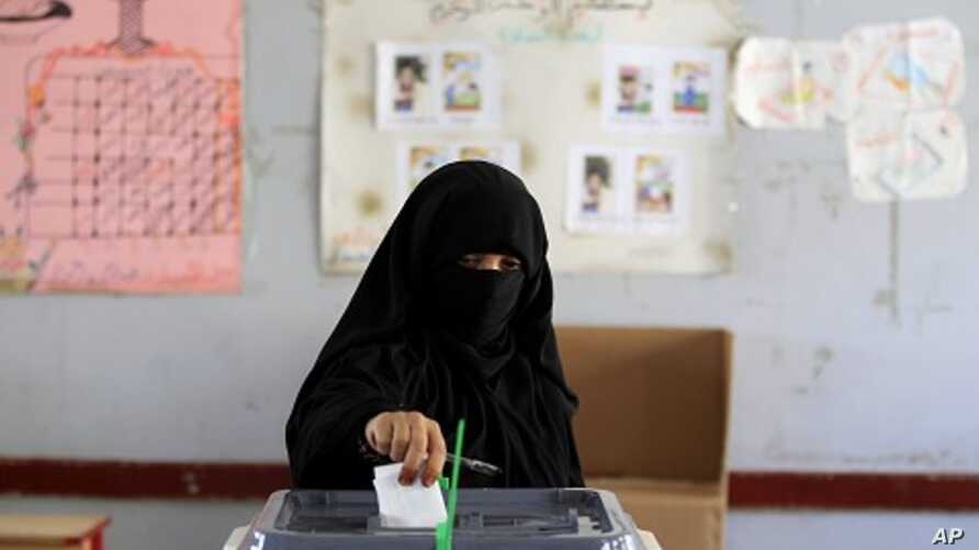 A woman casts her vote during the presidential elections at a polling station in Al Hasaba neighborhood in Sana'a February 21, 2012.