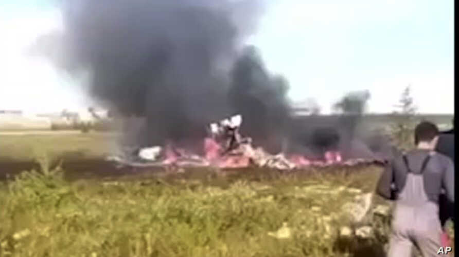 In this image made video, smoke rises from a crash side of a Russian helicopter Mi-8 crashed shortly after takeoff in Vankor, above the Arctic Circle in Siberia, Russia, Saturday, Aug. 4, 2018.