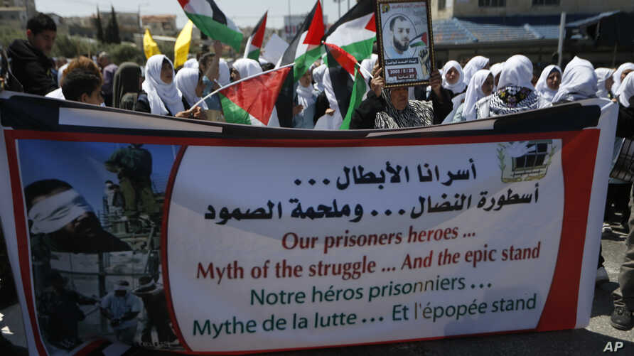 People hold banners during a rally in support of Palestinian prisoners in the West bank City of Bethlehem,  April 17, 2017.