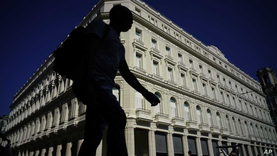 A man walks in front of the Manzana de Gomez Kempinski hotel in Havana, Cuba, May 8, 2017. In the heart of the capital of a nation founded on ideals of social equality, the business arm of the Cuban military has transformed a century-old shopping arc