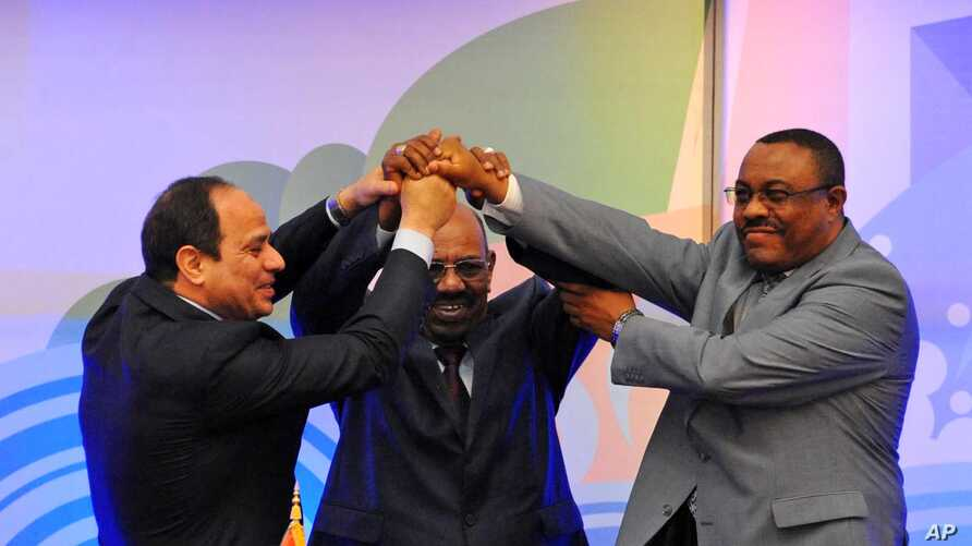 Sudanese President Omar al-Bashir, (c), Egyptian President Abdel-Fattah el-Sissi, (l), and Ethiopian Prime Minister Hailemariam Desalegn, (r), hold hands after signing an agreement on sharing water from the Nile River, in Khartoum, Sudan, March 23, 2