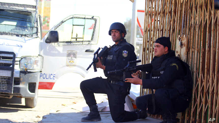 Tunisian police officers take positions as they search for attackers still at large in the outskirts of Ben Guerdane, southern Tunisia, March 8, 2016.