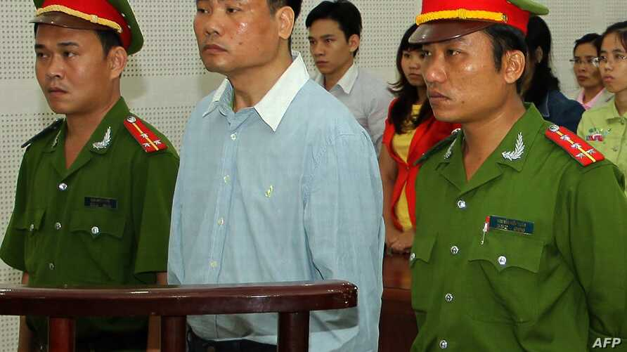 FILE - Blogger Truong Duy Nhat (C) stands trial at a local People's Court in the central city of Da Nang on March 4, 2014.