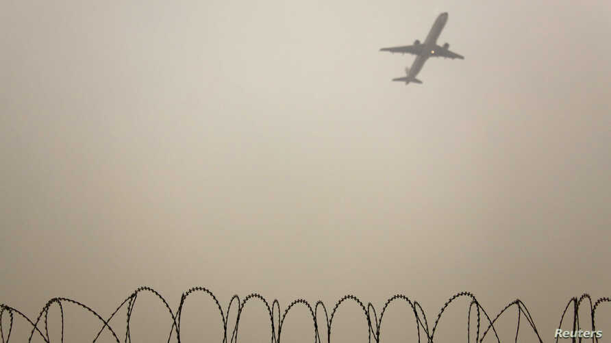 FILE - A plane flies in the polluted air above the airport fences in Beijing, Feb. 22, 2012.