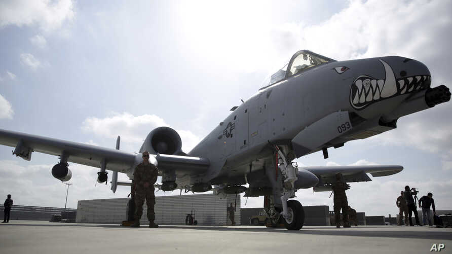 FILE - U.S. military personnel stand beside an A-10C fighter jet at Kandahar Airfield, Afghanistan, Jan. 23, 2018.