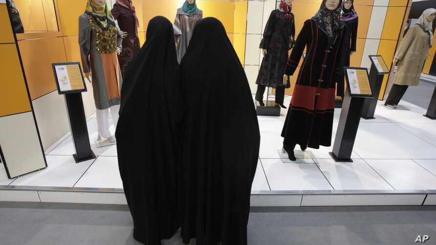 Head-to-toe veiled Iranian women look at mannequins in a women's dress show in Tehran, Iran, March 3, 2012. (AP)