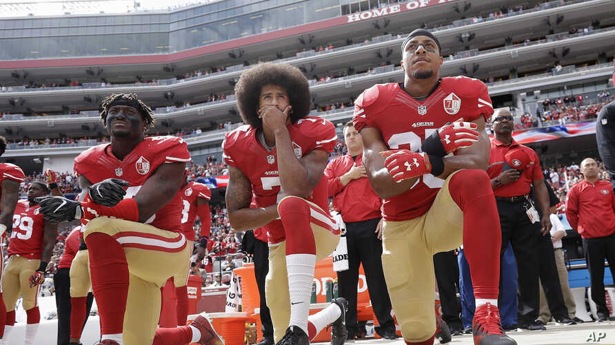 From left, San Francisco 49ers outside linebacker Eli Harold, quarterback Colin Kaepernick and safety Eric Reid kneel during the national anthem before an NFL football game against the Dallas Cowboys in Santa Clara, California, Oct. 2, 2016.