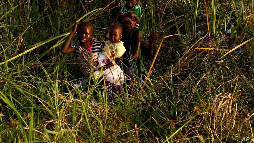 Children cross a swamp area to reach a registration area prior to a food distribution carried out by the United Nations World Food Programme (WFP) in Thonyor, Leer county, South Sudan, February 25, 2017. Picture taken February 25, 2017.
