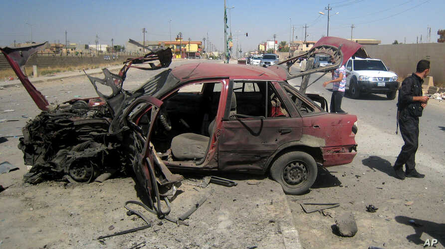 People inspect the site of a car bomb attack on cars lined up at a gas station in the oil rich city of Kirkuk, in northern Iraq, July 10, 2014.