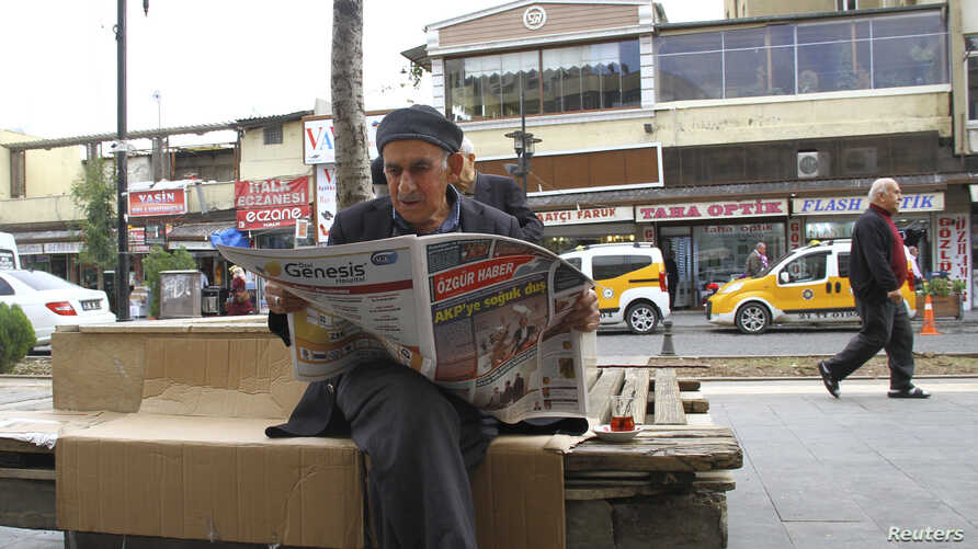 A man reads a newspaper as he sits on a bench in Sur district of the Kurdish dominated southeastern city of Diyarbakir, Turkey, Oct. 30, 2015.