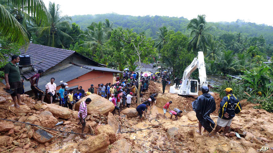 Sri Lankans watch military rescue efforts at the site of a landslide at Bellana village in Kalutara district, Sri Lanka, May 26, 2017. Mudslides and floods triggered by heavy rains in Sri Lanka killed dozens and left many more missing.
