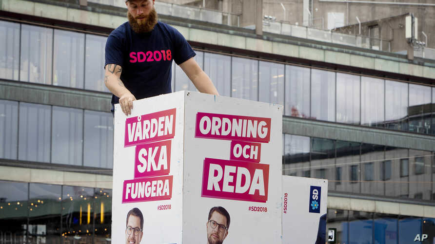 "Election posters of the Sweden Democrats are put up by a party member in Stockholm, Aug. 30, 2018. The poster for the Sept. 9, 2018, election reads, ""Welfare must work"" and ""Law and order."""