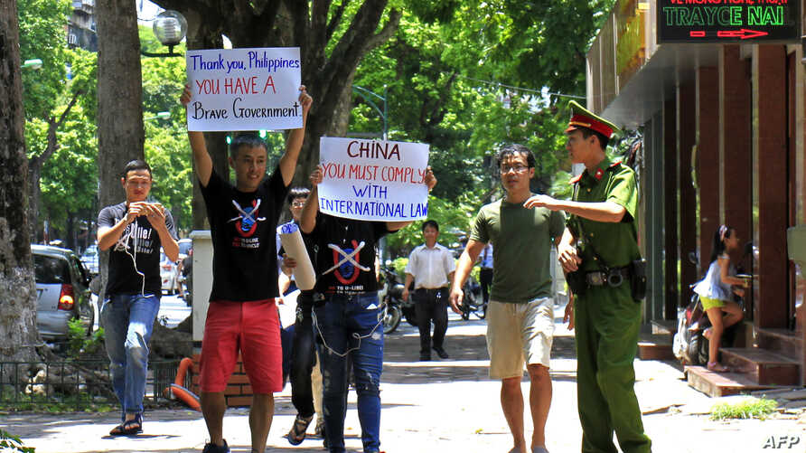 A policeman (R) reacts as demonstrating activists hold anti-China banners in Hanoi on July 17, 2016.