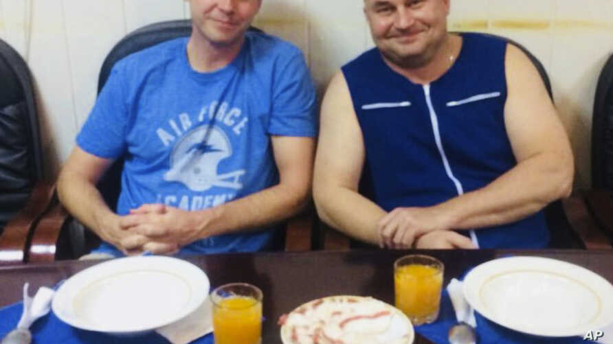 In this photo released by Roscosmos, NASA astronaut Nick Hague, left, and Roscosmos cosmonaut Alexei Ovchinin pose for a photo in Baikonur, Kazakhstan,  Oct. 11, 2018, after an emergency landing following the failure of a Russian booster rocket carry