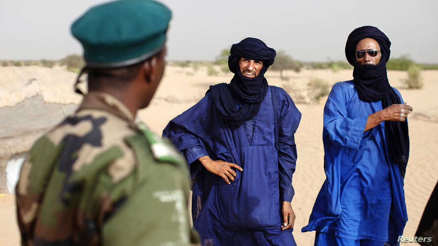 A Malian soldier speaks with Tuareg men Seydou (C) and Abdoul Hassan in the village of Tashek, outside Timbuktu, July 27, 2013.