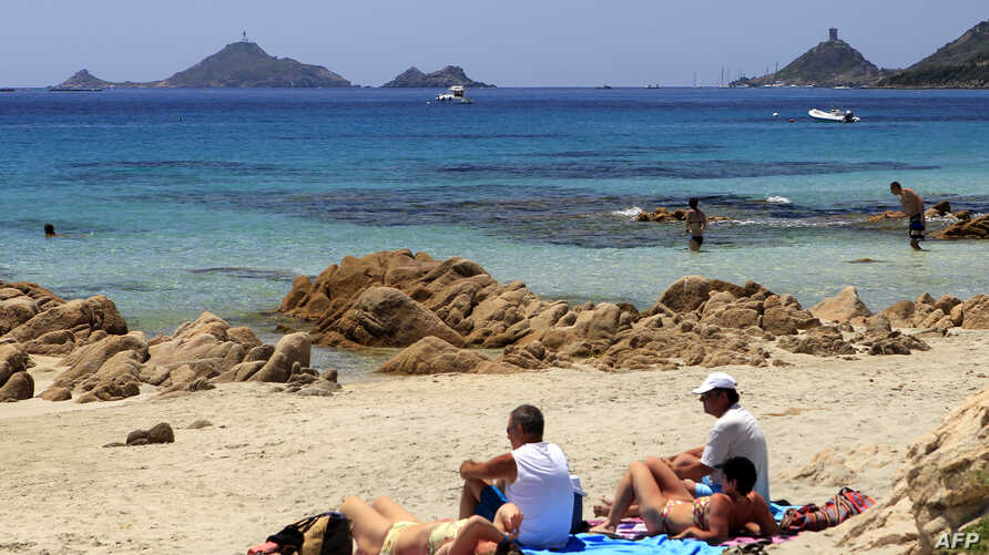 People sit on the Terre Sacree beach in Ajaccio on June 25, 2016 on the French island of Corsica.
