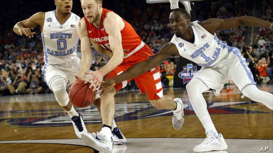 Syracuse's Trevor Cooney (10) drives against North Carolina's Nate Britt (0) and Theo Pinson (1) during the first half of the NCAA Final Four tournament college basketball semifinal game Saturday, April 2, 2016, in Houston. (AP Photo/David J. Phillip