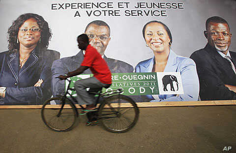 "A cyclist rides past a campaign poster of candidates of the Democratic Party of Ivory Coast in Abidjan December 6, 2011. The slogan on the poster reads ""Experience and youth at your service."""