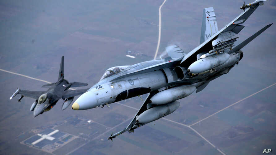 A Portuguese military fighter jet, left, and a Canadian military fighter jet participating in NATO's Baltic Air Policing Mission operate in Lithuanian airspace, Nov. 20, 2014.