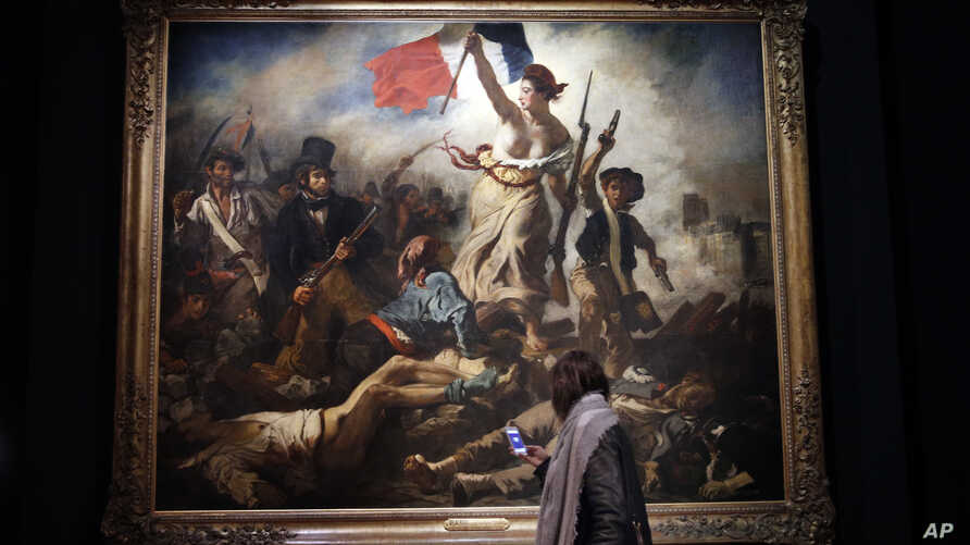 """A woman looks at """"La liberte guidant le peuple"""" (""""Liberty Leading the People"""") by Eugene Delacroix at the Louvre, in Paris, March 27, 2018. The Louvre is presenting a retrospective of Delacroix's work."""