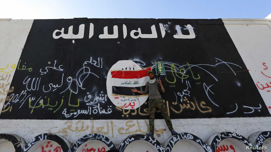 FILE - A member of militias known as Hashid Shaabi stands next to a wall painted with the black flag commonly used by Islamic State militants, in the town of al-Alam, Iraq.