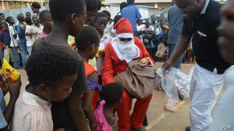 Santa Clause shares sweets and other gifts with students (VOA/L. Masina)