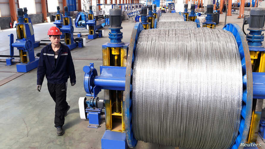 A worker walks past aluminium wires at a plant inside an industrial park in Binzhou, Shandong province, China, April 7, 2018.