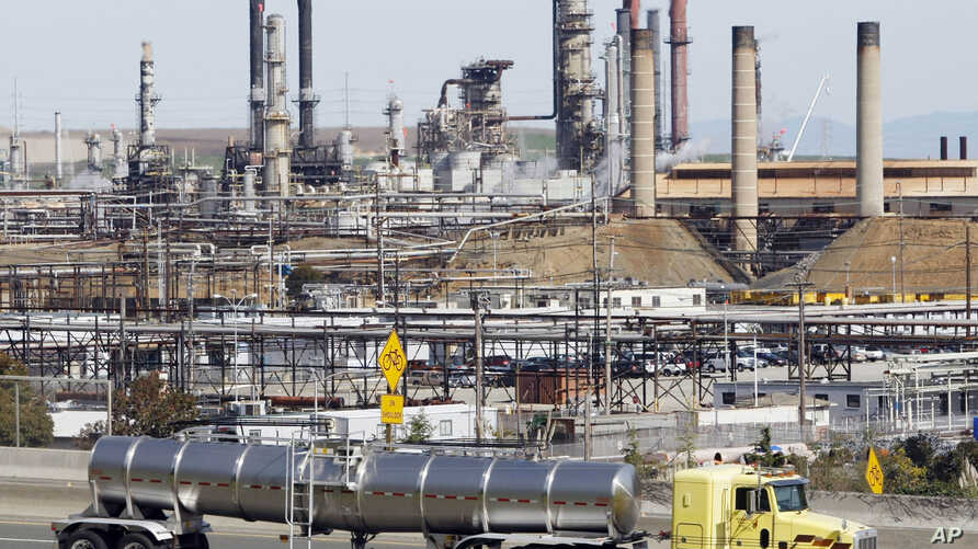FILE - In this March 9, 2010, photo, a tanker truck passes an oil refinery in Richmond, California. Vowing to keep the United States on track to meet its emissions-cutting target, an alliance of states, cities and businesses  have pledged  to stay in