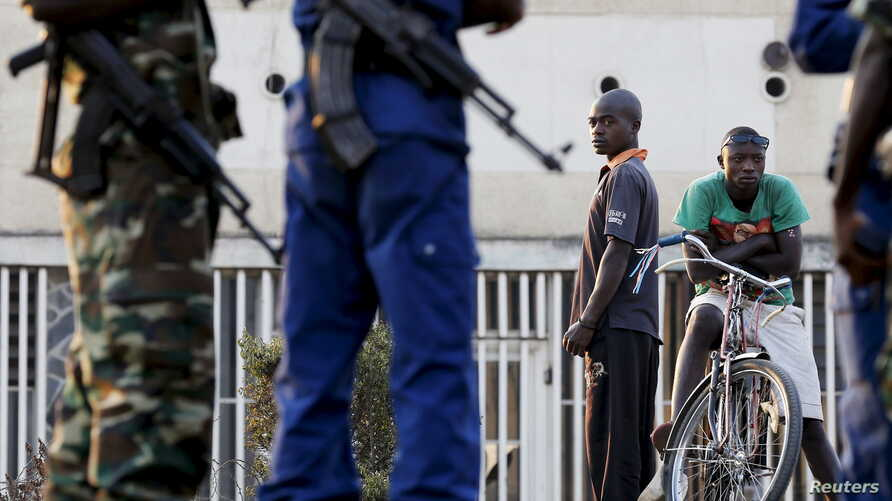 Residents look on as police and soldiers guard a voting station in Burundi's capital Bujumbura during the country's presidential elections, July 21, 2015.
