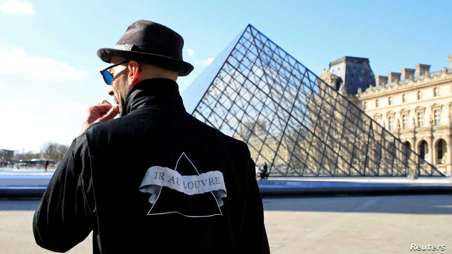 French artist JR works in the courtyard of the Louvre Museum near the glass pyramid designed by Ieoh Ming Pei as the Louvre Museum celebrates the 30th anniversary of its glass pyramid in Paris, France, March 26, 2019.