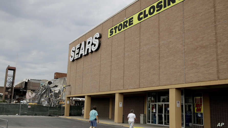 In this July 8, 2017, file photo people walk into a Sears store slated for closing that is next to a mall that is being torn down in Overland Park, Kan. Sears has filed for Chapter 11 bankruptcy protection Monday, Oct. 15, 2018.