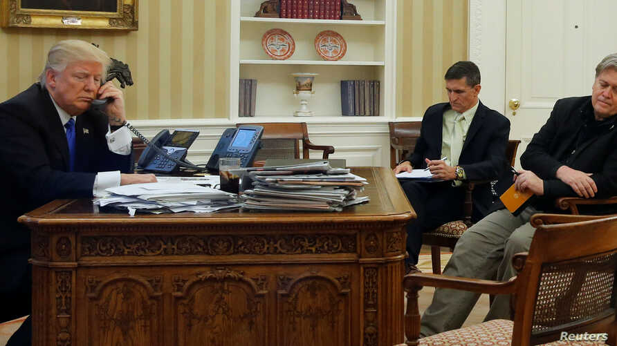 U.S. President Donald Trump, seated at his desk with National Security Advisor Michael Flynn and senior advisor Steve Bannon, right, speaks by phone with Australia's Prime Minister Malcolm Turnbull in the Oval Office at the White House, Jan. 28, 2017...