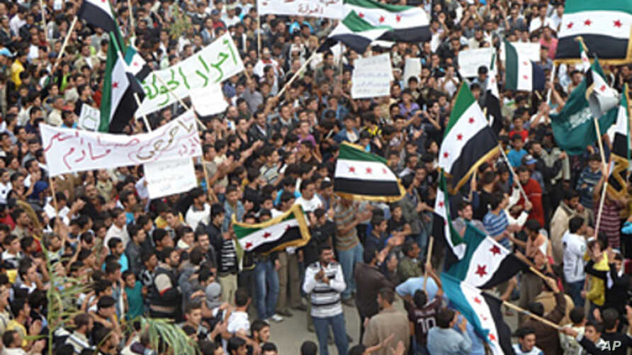 Demonstrators protesting against Syria's President Bashar al-Assad march through the streets after Friday prayers in Hula, near Homs, October 28, 2011.