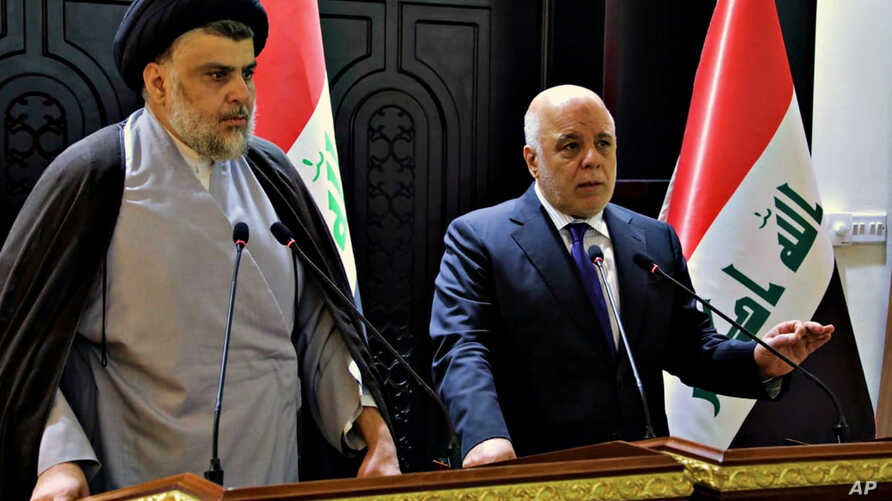 In this photo provided by the Iraqi government, Iraqi Prime Minister Haider al-Abadi, right, and Shiite cleric Muqtada al-Sadr hold a press conference in the heavily fortified Green Zone in Baghdad, Iraq, May 20, 2018.