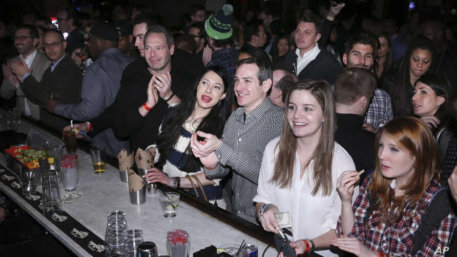 """FILE - Guests gather to watch the Super Bowl, Feb. 2, 2014, in New York. During flu season, """"Anytime that you have large groups of people congregating in enclosed spaces you know it always offers an opportunity for more efficient spread of germs,"""" an"""