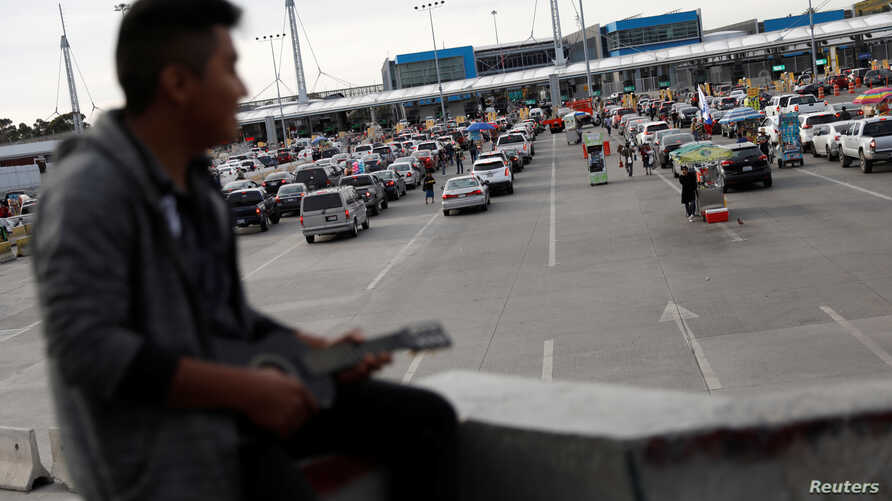 A man sits as cars queue up in multiple lines waiting to be inspected by U.S. border patrol officers to enter from Mexico into the U.S., at the San Ysidro port of entry, in Tijuana, Mexico, April 3, 2019.