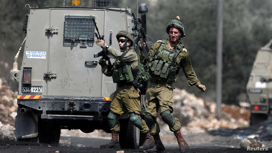 A stone is thrown at an Israeli soldier during clashes with Palestinians following a protest against the near-by Jewish settlement of Qadomem, in the West Bank village of Kofr Qadom near Nablus, Aug. 25, 2017.