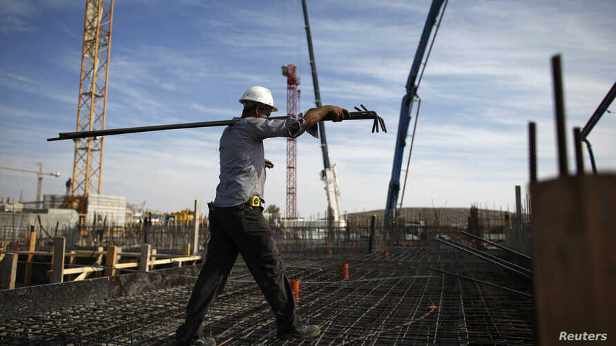 FILE - A laborer works on an apartment building project in a Jewish settlement known to Israelis as Har Homa and to Palestinians as Jabal Abu Ghneim in an area of the West Bank that Israel captured in the 1967 war and annexed to Jerusalem, Oct. 28, 2...