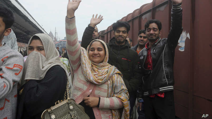 Pakistani family waves to their Indian relatives, who are leaving to return to India, after being stranded in Pakistan for a week, at Lahore Railway Station in Pakistan, Monday, March 4, 2019.